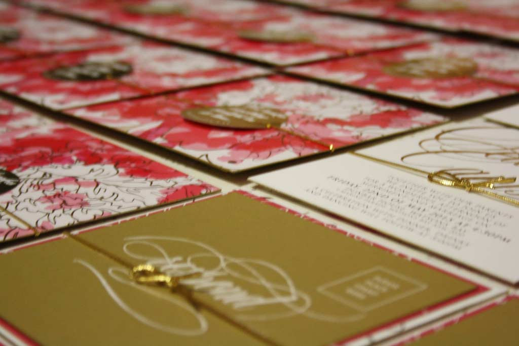 A picture of wedding invitations being assembled by Pocadot Invitations